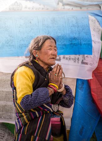 reside: LHASA, TIBET - MAY 2016 - A woman prays in front of Jokhang temple as a part of her pilgrimage during Sagadawa festival in Lhasa, Tibet. Tibetans celebrate Sagadawa festival in May by visiting temples and praying.