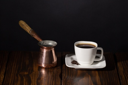 Cup of coffee and turkish pot  Dark scene on wooden background