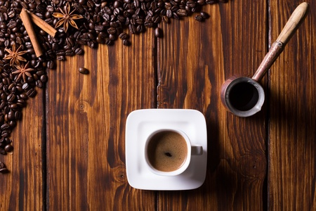 Still life with coffee beans, cup of coffee, turkish pot and spices on dark wooden background  Top view  Stock Photo - 20790795