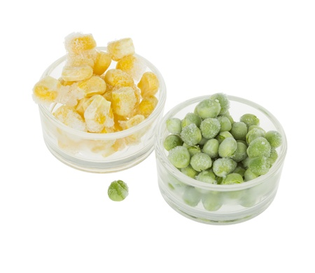 Two Small Glass Cups With Frozen Corn And Frozen Peas isolated on white photo