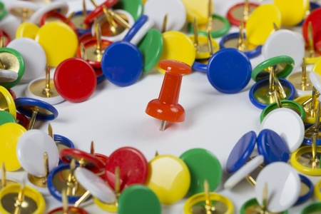 Many colorful pushpins with red one in the middle