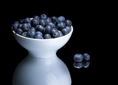 Blueberries in white bowl on a mirror  Isolated on black