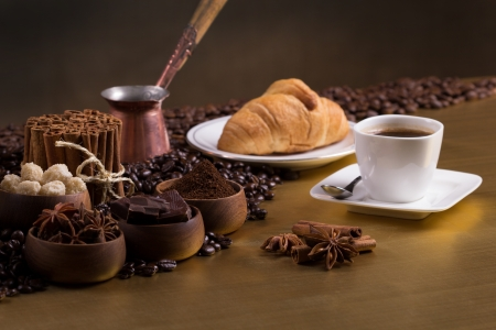 Wooden bowls with coffee beans, sugar, anise, chocolate Cinnamon bunch, croissant and cup of coffee