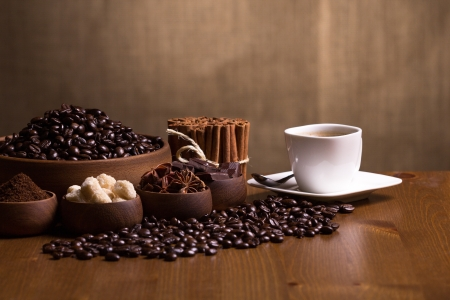 Wooden bowls with coffee beans, sugar, anise, chocolate, Cinnamon bunch and coffee cup  Stock Photo - 20870512
