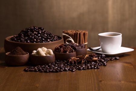 Wooden bowls with coffee beans, sugar, anise, chocolate, Cinnamon bunch and coffee cup