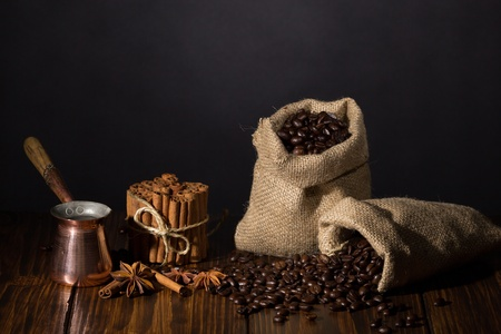 Two small sacks with coffee, spices and copper turkish pot on wooden background  Stock Photo - 20870481