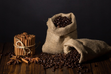 Two small sacks with coffee, spices on wooden background Stock Photo - 20870436