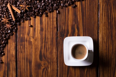 coffee beans, cup of coffee, and spices on dark wooden background Stock Photo - 20870440