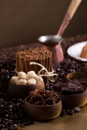 Wooden bowls with coffee beans, sugar, anise, chocolate  Cinnamon bunch, turkish pot and cup of coffee Stock Photo - 22924355
