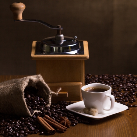 Still-life with coffee, cup with saucer, coffee mill, sac with beans and spices Stock Photo - 22924353