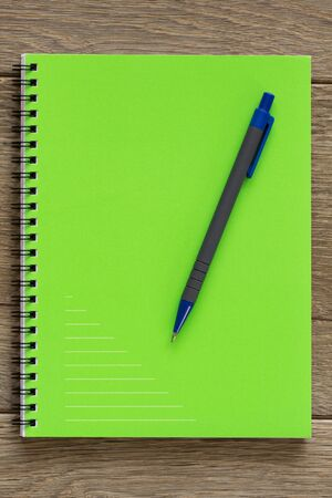 Green notebook on wooden desk photo