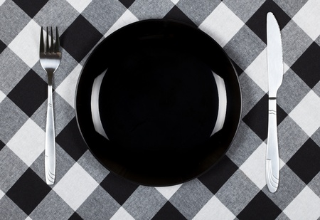 Fork and knife with black plate on checkered tablecloth  photo