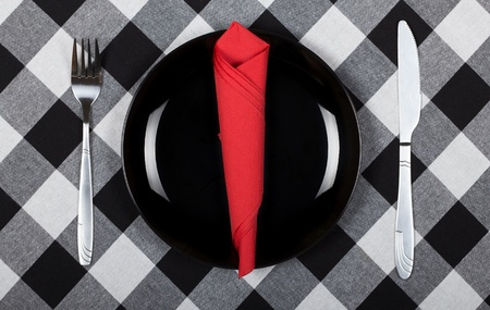 Red napkin on black plate  Checkered b w tablecloth  photo