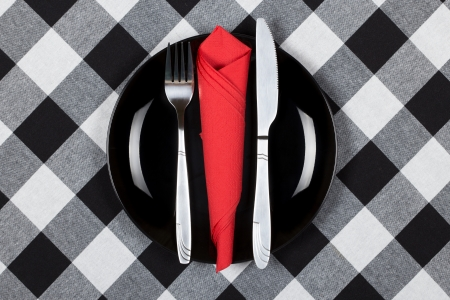 Fork, knife and red napkin on black plate  Checkered black and white tablecloth  photo