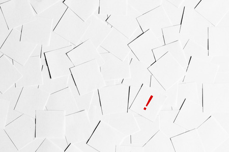Note paper with exclamation mark on a pile of blank papers photo