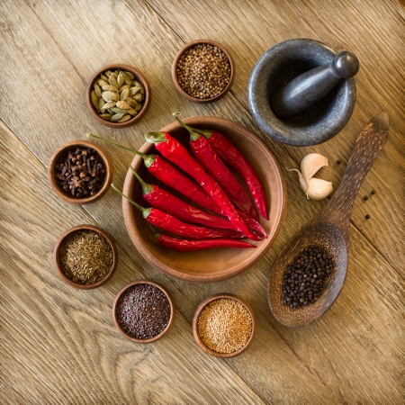 Spices in wooden bowls and mortar with pestle photo
