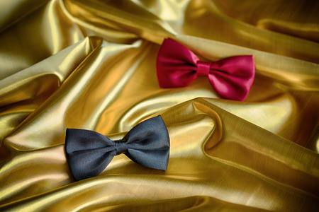 Red and black bow ties on draped golden satin photo