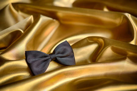 Black bow tie on draped golden satin photo