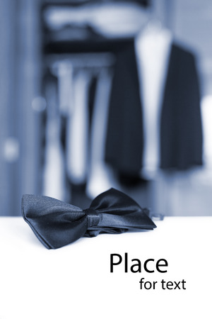 Bow tie  Open closet and tuxedo  Getting ready for formal night  Colorized shot with isolated place for text  photo
