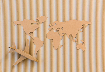 Airplane and world map made of cardboard  Worldwide delivery concept