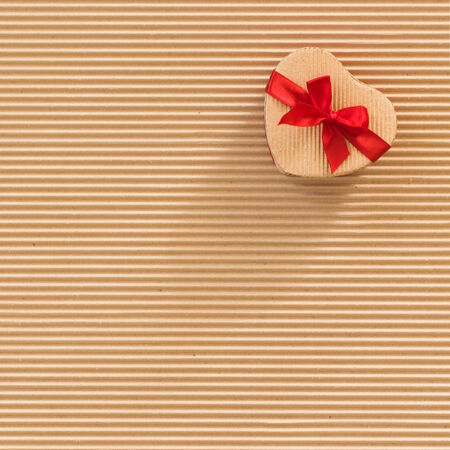 Cardboard gift box with red bow, heart shaped, on corrugated cardboard background, square format  photo