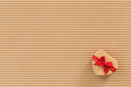 Heart shaped gift box with red ribbon and bow on corrugated cardboard background  photo