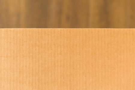 Corrugated cardboard on blurry brown background photo