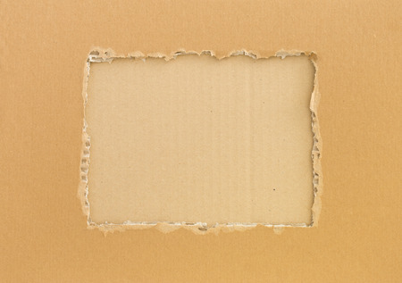 Frame of torn cardboard with corrugated cardboard background  photo