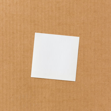 White paper note on corrugated cardboard background photo