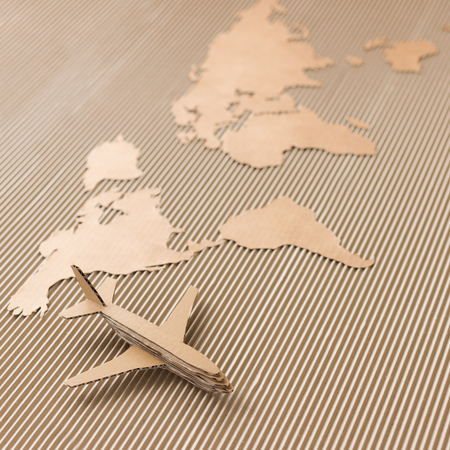 Airplane and world map made of cardboard  Square format, selective DOF Stock Photo