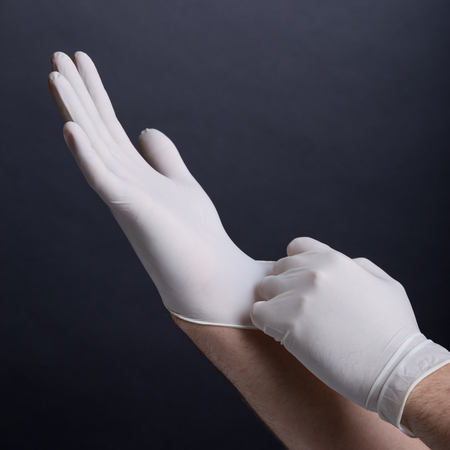 woman's hands: Male hands putting on latex gloves on dark background