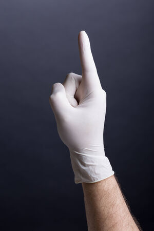 Male hand in latex glove  finger up  on dark background photo