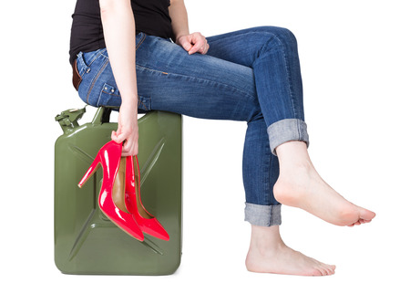 Girl sitting on a jerrycan with red heels in hand
