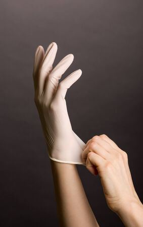 latex gloves: Female hands putting on latex gloves on dark background
