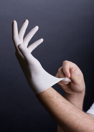 Male hands putting on latex gloves on dark background photo