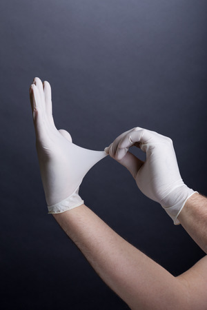 Male hands in latex gloves on dark background Stock Photo