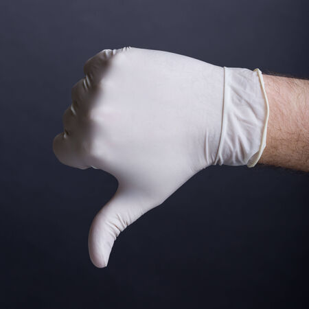 Male hand in latex glove  thumb down sign  on dark background photo