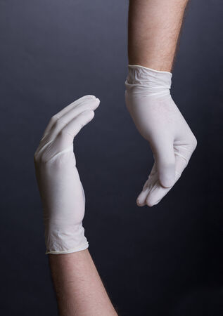 Male hands in latex gloves carries on dark background photo