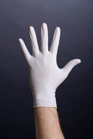 Male palm in latex glove on dark background photo