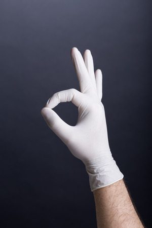 Male hand in latex glove  OK sign  on dark background photo