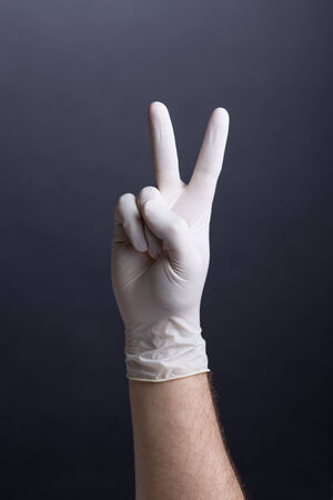 Male hand in latex glove  victory gesture, v-sign  on dark background photo
