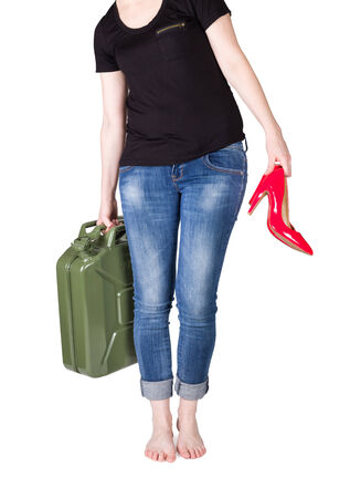 Woman with jerrycan in one hand and red pumps in another one isolated on white  photo