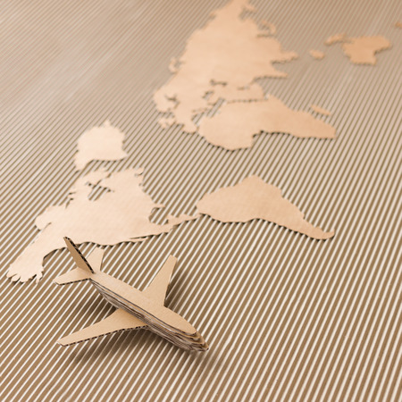 Airplane and world map made of cardboard  Square format, selective DOF photo