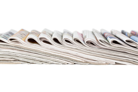 Assortment of folded newspapers isolated on white photo
