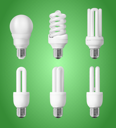 Set of energy saving light bulbs on green background