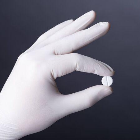 latex glove: Hand in white latex glove holding white pill on dark background