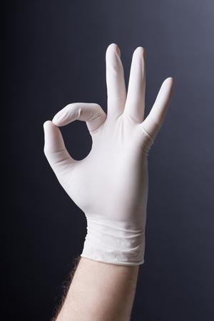 latex glove: Male hand in latex glove OK sign on dark background Stock Photo