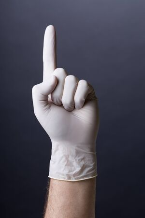 latex glove: Male hand in latex glove pointing up on dark background Stock Photo