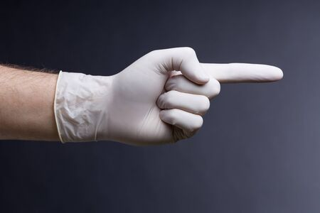 latex glove: Male hand in latex glove on dark background