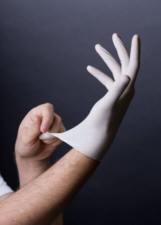 latex gloves: Male hands in golves. Doctor or nurse putting on latex gloves. Sanitary, healthcare, medical clothing. Dark background